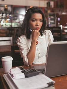 young female business owner sitting at table with laptop, coffee, calculator and business papers