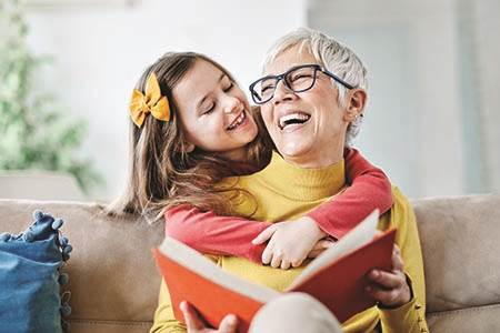 grandma sitting on couch laughing with young granddaughter while reading a book