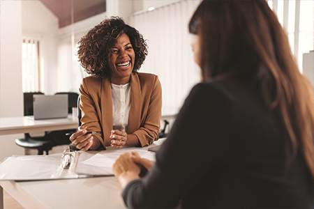 smiling female business owner sitting at desk with female banker talking about business credit cards